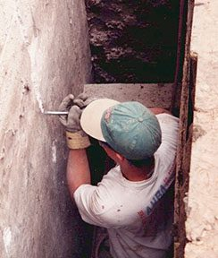 man-chipping-away-cracked-foundation