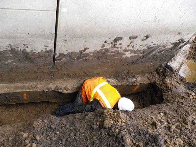 Construction worker in trench near a concrete wall