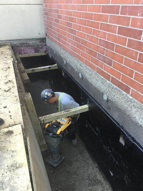 Man working in trench near brick building